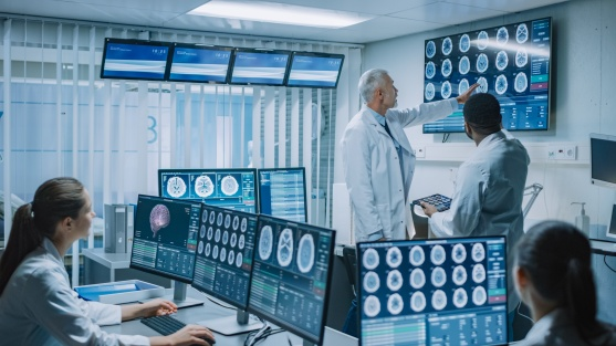 Team of Professional Medical Scientists Work in the Brain Research Laboratory. Neurologists / Neuroscientists Surrounded by Monitors Showing CT, MRI Scans Having Discussion and Working on PС
