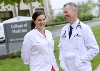 a woman and a man stand in front of a sign for the Penn State college of medicine. Both are wearing white lab coats and smiling