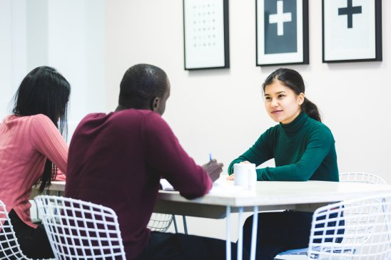 three people sitting around a table in a group discussion