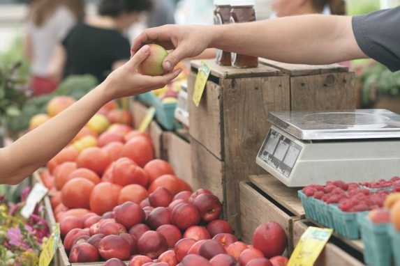 close up of two peoples' arms at a fruit stand; one person is handing an apple to the other