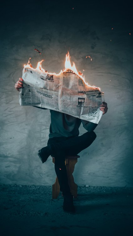 a person is sitting cross-legged while reading a newspaper that is on fire; the person's face is hidden