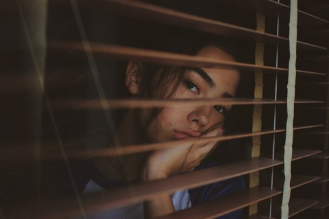 young girl in a dark room rests her face in her hand as she looks out between the slats of window blinds