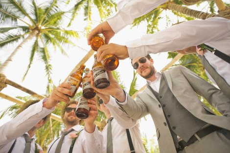 six people in casual business attire stand under palm trees and clink brown bottles together