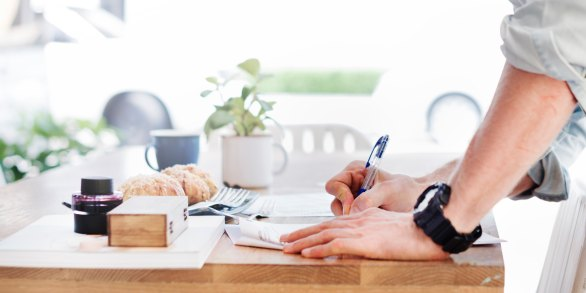 person with rolled-up sleeves leans on a desk surface to write, with mugs and pastries in the background